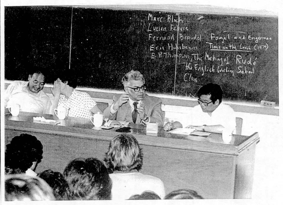 Georg Iggers sitting with chinese colleagues in front of an audience. Blackboard in the background.